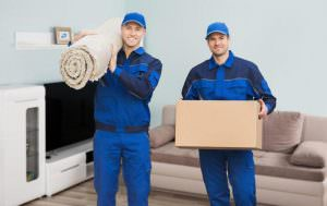 Moving Men Inside a house carrying a roll of carpet and boxes