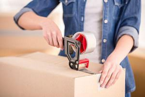 Packing Supplies and Services offered. Woman taping up moving box