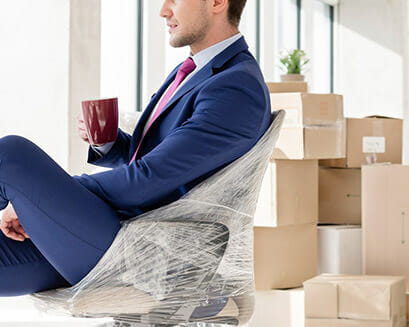 man sits in office with moving boxes